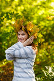 Happy young woman with autumn maple leaves garland in park. Happy young woman with autumn maple leaves garland in park royalty free stock images