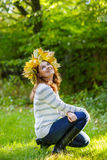 Happy young woman with autumn maple leaves garland in park. Happy young woman with autumn maple leaves garland in park stock photography