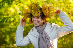 Happy young woman with autumn maple leaves garland in park. Stock Photography
