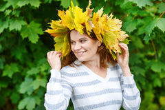 Happy young woman with autumn maple leaves garland in park. Stock Photo
