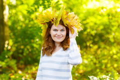 Happy young woman with autumn maple leaves garland in park. Girl enjoying warm october fall day. Beautiful colors and bright light royalty free stock photography