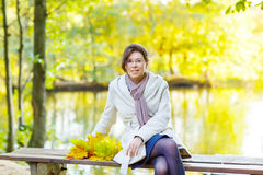 Happy young woman with autumn maple leaves garland in park. royalty free stock photography