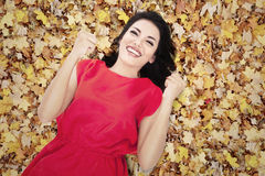 Happy young woman in autumn orange leaves. A happy young woman lying on autumn orange leaves royalty free stock photo