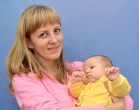 The happy young woman with the baby on a blue background Royalty Free Stock Photos