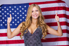 Happy young woman on a background of the American flag Royalty Free Stock Photos