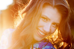 Happy young woman on background of the glowing Sun close up Stock Images