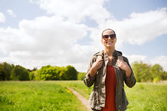 Happy young woman with backpack hiking outdoors Stock Photo