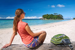 Happy young woman with backpack relaxing on coast and looking to Royalty Free Stock Photos