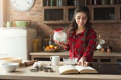 Happy young woman baking in loft kitchen. Happy young woman baking pie in loft kitchen at home, using book with recipe. Mockup, copy space Royalty Free Stock Photo