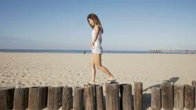 Happy young woman balance at wood bollards. summer feeling stock footage