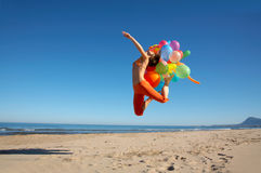 Happy young woman with balloons jumping. Happy young woman with different colored balloons jumping on the beach Stock Images