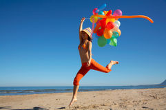 Happy young woman with balloons jumping. Happy young woman with different colored balloons jumping on the beach Stock Photos