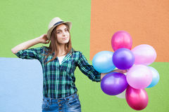 Happy young woman with balloons near colorful wall. Happy young woman in hat with balloons near colorful wall Royalty Free Stock Photo