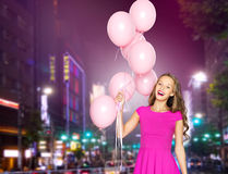 Happy young woman with balloons over night city Royalty Free Stock Images