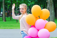 Happy young woman with balloons. Portrait of smiling teenager model posing and waving her hand to camera holding bright and colorful balloons in the park stock photos