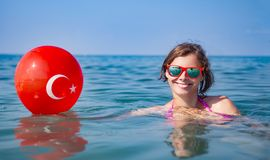 Happy young woman bathing in blue sea water and holds balloon with turkish flag. Resorts in Turkey stock image