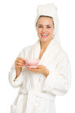 Happy young woman in bathrobe with cup of coffee Royalty Free Stock Photography