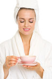 Happy young woman in bathrobe enjoying cup of tea Stock Photos
