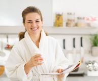 Happy young woman in bathrobe with glass of milk Stock Image
