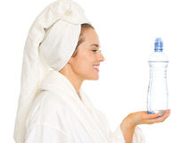 Happy woman in bathrobe holding bottle with water Stock Photography