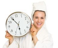 Happy young woman in bathrobe holding clock Royalty Free Stock Image