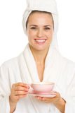Happy young woman in bathrobe holding cup of tea Stock Image