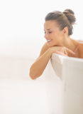 Happy young woman in bathtub looking on copy space. Happy young brunette woman in modern bathtub looking on copy space stock image