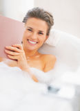 Happy young woman in bathtub reading book Stock Image