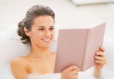Happy young woman in bathtub reading book Royalty Free Stock Image