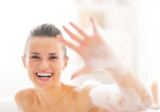 Happy young woman in bathtub showing foam Stock Photos