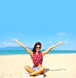 Happy young woman on a beach with arms raised Royalty Free Stock Photography
