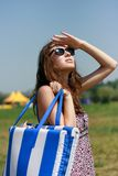 Happy young woman with beach bag Royalty Free Stock Images