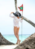 Happy young woman on the beach and flag Maldives Royalty Free Stock Photo