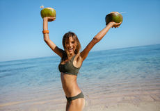 Happy young woman on the beach with fresh coconuts. Portrait of happy young woman on the beach with fresh coconuts in hand. Female model in bikini standing on Royalty Free Stock Photo
