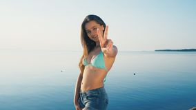 Happy young woman at beach. Girl tourist is wearing bikini on vacation gesturing peace sign at camera royalty free stock photography
