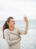 Happy young woman on beach taking self photo using cell phone Stock Photo