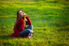Happy young woman. Beautiful female with long healthy hair enjoying sun light in park sitting on green grass. Spring Stock Photo