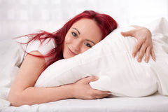 Happy young woman in bed. Cuddling with pillow Royalty Free Stock Images