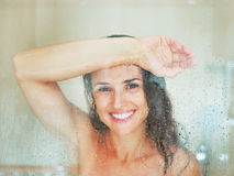 Happy young woman behind shower door Royalty Free Stock Photos