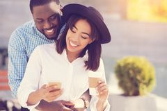 Happy young woman being hugged by her boyfriend. Being loved. Happy nice young women smiling and holding her smartphone while being hugged by her boyfriend stock images