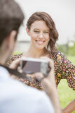 Happy young woman being photographed by man in park Royalty Free Stock Photo