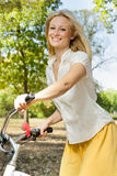 Happy young woman on the bicycle Stock Image