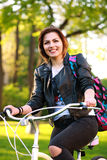Happy young woman on bicycle in green park on sunset Stock Photo