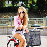 Happy young woman on a bicycle in summertime Stock Photo