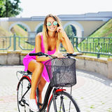 Happy young woman on a bicycle in a summertime Stock Photo