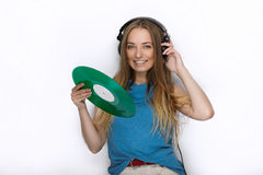 Happy young woman in big black professional dj headphones holding trendy green colorful vinyl record posing against white studio b Royalty Free Stock Photo