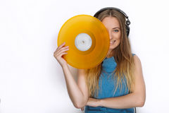 Happy young woman in big black professional dj headphones holding trendy yellow colorful vinyl record posing against white studio Stock Photo