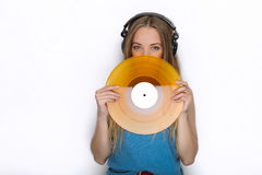 Happy young woman in big black professional dj headphones holding trendy yellow colorful vinyl record posing against white studio Stock Images