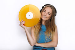 Happy young woman in big black professional dj headphones holding trendy yellow colorful vinyl record posing against white studio Stock Image