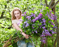 Happy young woman with big bouquet of lilac Royalty Free Stock Images